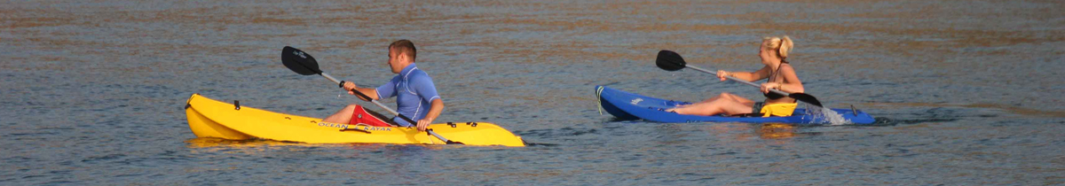 A female and male kayaking on open water